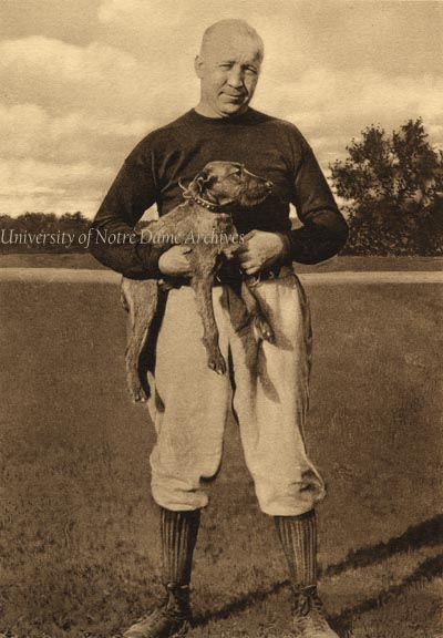 """GNDL 38/04: Football Coach Knute Rockne holding an Irish terrier dog, 1924. [1927 Calendar August stylized photo] A 1924 Football Program calls the Irish terrier mascot dog Tipperary Terrence II. See also GATH 4/11. Original caption: """"Head Coach Knute Rockne of the Notre Dame football team with 'Terry' the winning mascot, who will be present at the contest with the Army at the Polo Grounds. Date Photographed: October 17, 1924 ACME Newspictures 10580"""" Image also claimed by © Bettmann/CORBIS, U262190INP (Rights Managed)"""